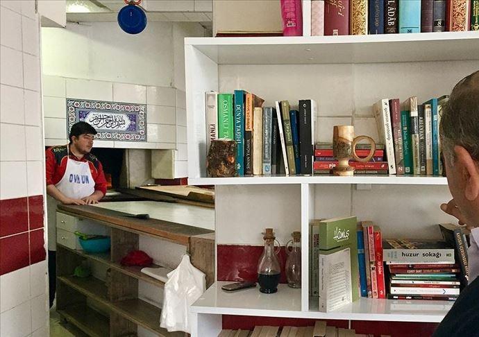 Etli ekmek fırınında müşteriler kitap okuyarak sıra bekliyor